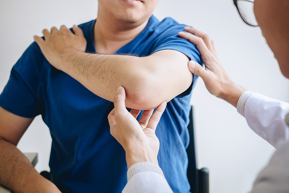 Doctor physiotherapist assisting a male patient while giving exercising treatment massaging the arm of patient in a physio room