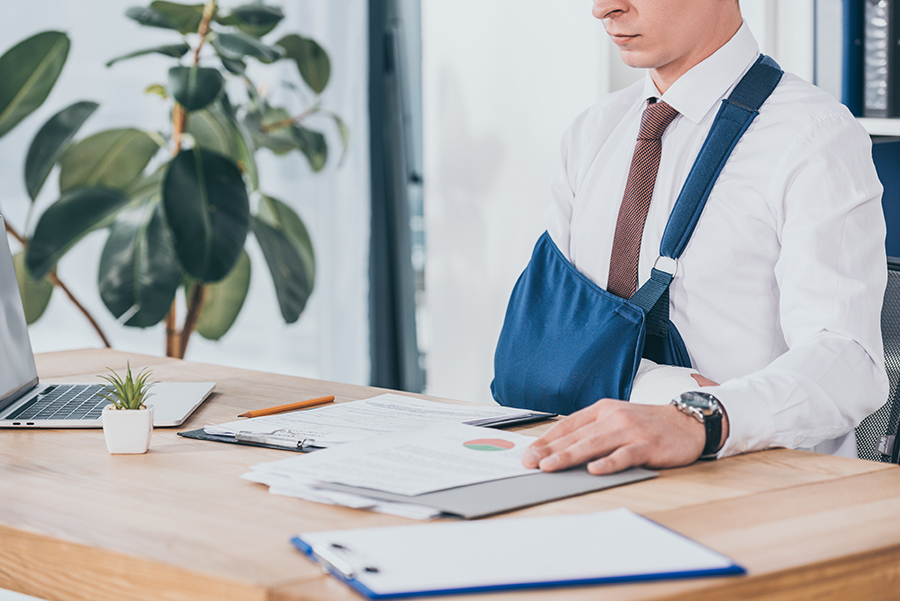 Worker with broken arm in bandage sitting at table and reading documents in office