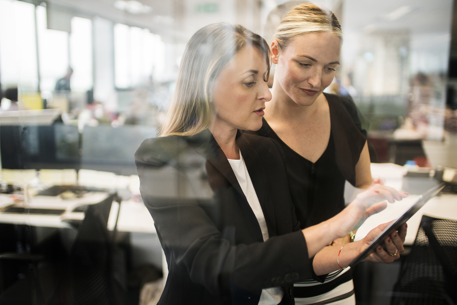 Businesswomen working together behind glass wall with reflections